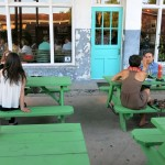 Bright green tables, and bright turquoise doors - it's a great combination. Photo by Sarah Corbitt